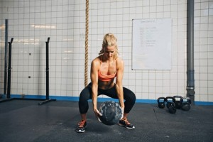 Fit and strong female athlete working out with a medicine ball to get better core strength and stability. Woman doing crossfit workout at gym.