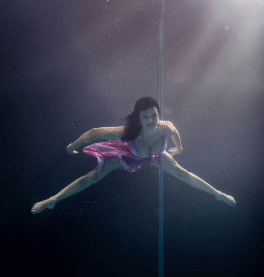 PIC BY BRETT STANLEY/ CATERS NEWS - (PICTURED: Pole dancer Phyllisann) - A photographer has made a splash with his spectacular images of underwater pole dancers. Brett Stanley captured the beauty and talent of his subjects as they gracefully danced in the water. Shot over a few weeks in conjunction with pole dance supplier X-Pole, he worked with the dancers to create the series. Brett taught them how to hold their breath under the water and collaborated on which poses looked best.