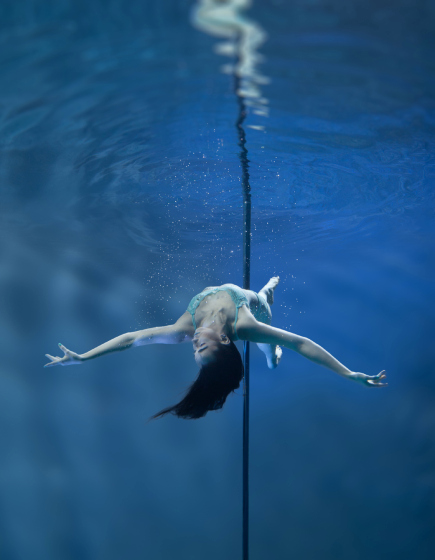PIC BY BRETT STANLEY/ CATERS NEWS - (PICTURED: Pole dancer June) - A photographer has made a splash with his spectacular images of underwater pole dancers. Brett Stanley captured the beauty and talent of his subjects as they gracefully danced in the water. Shot over a few weeks in conjunction with pole dance supplier X-Pole, he worked with the dancers to create the series. Brett taught them how to hold their breath under the water and collaborated on which poses looked best.