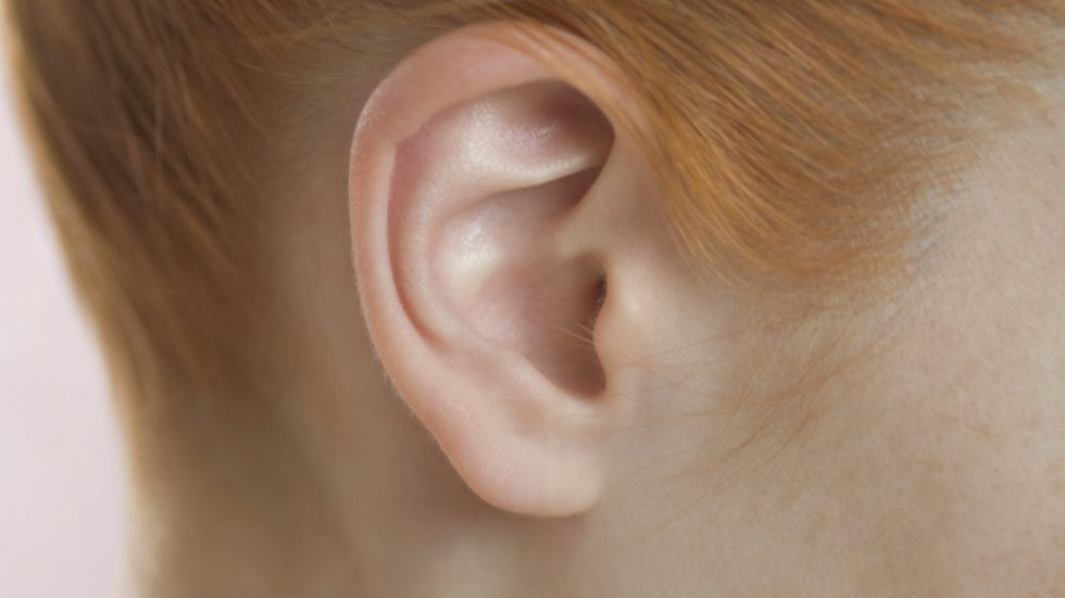 Detail of a redheaded woman's ear and neck