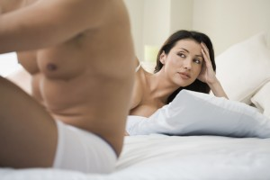 Anxious woman looking at boyfriend on bed