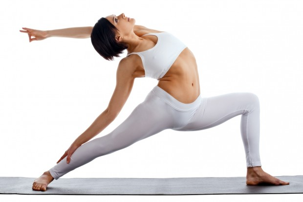 young woman training in yoga pose on rubber mat isolated