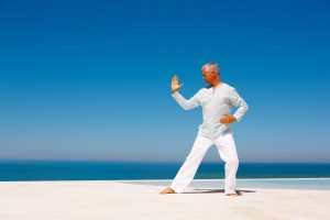 Portrait of an elderly man practicing martial arts on the beach