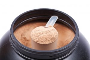 Scoop of chocolate whey isolate protein in a black plastick containter on white