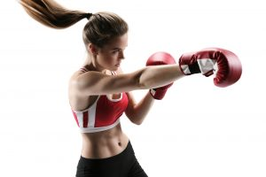 Boxer woman during boxing exercise making direct hit with red glove / photo set of sporty muscular female brunette girl wearing sports clothes over white background